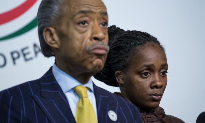 Kimberly Michelle Ballinger, domestic partner of Akai Gurley, who was shot by an NYPD officer, is joined by Rev. Al Sharpton at the National Action Network in New York on Nov. 22. (AP Photo/Craig Ruttle)