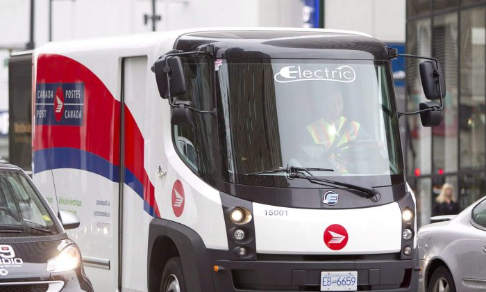 A Canada Post truck makes deliveries in Vancouver. The crown corporation is on track to make a profit in 2014 after a solid third quarter. (The Canadian Press/Jonathan Hayward)