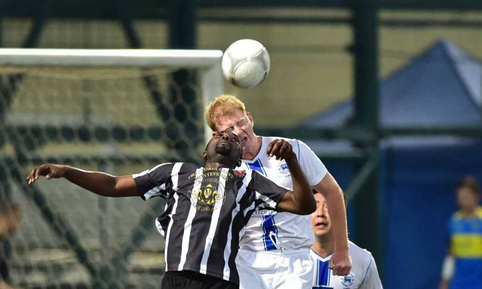 Albions Tom Pugh (white kit) heads clear in their 1-nil win over Corinthians in the Yau Yee league first division at Sports Road on Sunday Nov 23. (Bill Cox/Epoch Times)