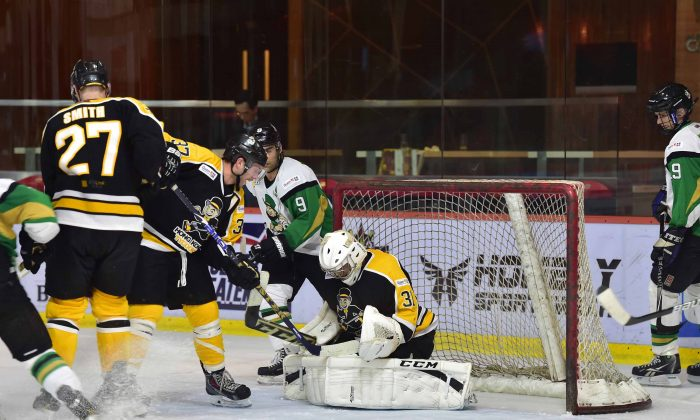 Hong Kong Tycoons goal scorers Brad Smith (27) and Kory Falite (37) back in defence to help goalie King Ho stave off an attack by the Macau Aces in the CIHL league at Mega Ice on Saturday Nov. 22, 2014. (Bill Cox/Epoch Times)