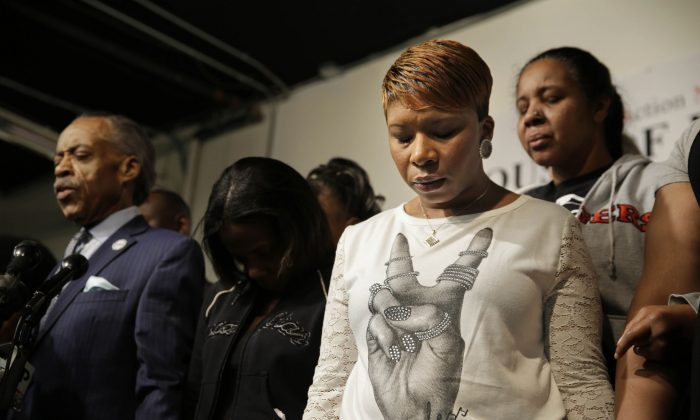 Lesley McSpadden (2R), mother of Michael Brown, prays with other families and Al Sharpton (L), at the National Action Network headquarters in New York, Wednesday, Nov. 26, 2014. On the day before Thanksgiving, Sharpton brought together the families of Michael Brown, Eric Garner and Akai Gurley, all black men recently killed by police officers. (AP Photo/Seth Wenig)