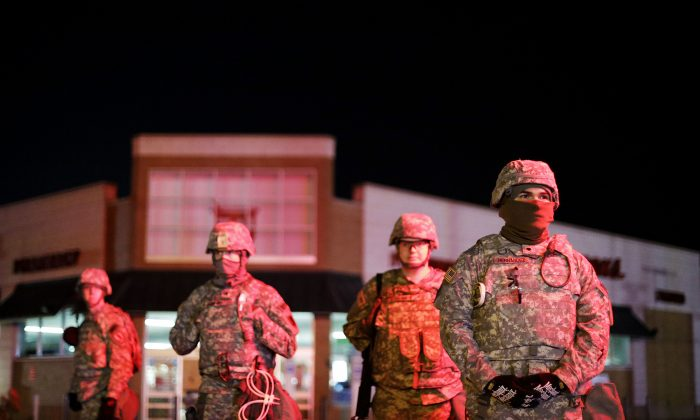 Missouri National Guard stand watch outside a Walgreens store, Wednesday, Nov. 26, 2014, in Ferguson, Mo. Missouri's governor ordered hundreds more state militia into Ferguson on Tuesday, after a night of protests and rioting over a grand jury's decision not to indict police officer Darren Wilson in the fatal shooting of Michael Brown, a case that has inflamed racial tensions in the U.S. (AP Photo/David Goldman)