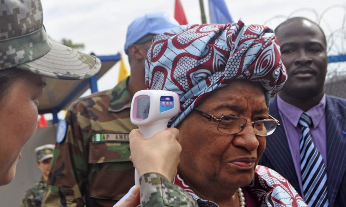 "Liberian President Ellen Johnson Sirleaf (C) temperature is taken by a Chinese soldier (L) before the opening of a new Ebola virus clinic in Monrovia, Liberia, Tuesday, Nov. 25, 2014. Liberia got another 100 treatment beds in the fight against Ebola on Tuesday, as yet another Sierra Leonean doctor became infected with the disease sweeping West Africa. Liberian President Ellen Johnson Sirleaf toured the Ebola treatment center built by China, calling it ""first-class."" (AP Photo/Abbas Dulleh)"