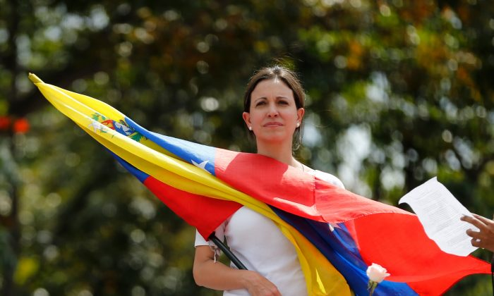 Opposition leader and Congresswoman Maria Corina Machado holds a Venezuelan flag during a women's protest outside the Bolivarian National Guard headquarters in Caracas, Venezuela, on Feb. 26, 2014. The outspoken leader of Venezuela's opposition is being charged, Nov. 26, 2014, in what the government alleges was a US-backed plot to assassinate President Nicolas Maduro. (AP Photo/Fernando Llano)