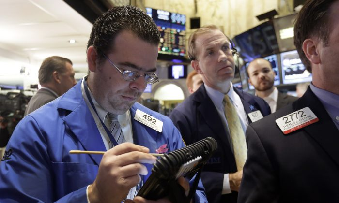 Traders Richard Scardino (L) and Michael Smyth work on the floor of the New York Stock Exchange, Wednesday, Nov. 26, 2014. Stock indexes are holding near record levels as traders digest some mixed news on the US economy. (AP Photo/Richard Drew)