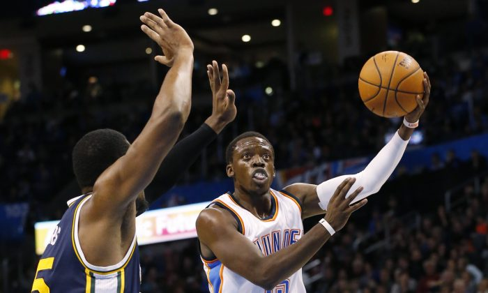 Oklahoma City Thunder guard Reggie Jackson, right, shoots in front of Utah Jazz forward Derrick Favors, left, in the first quarter of an NBA basketball game in Oklahoma City, Wednesday, Nov. 26, 2014. (AP Photo/Sue Ogrocki)