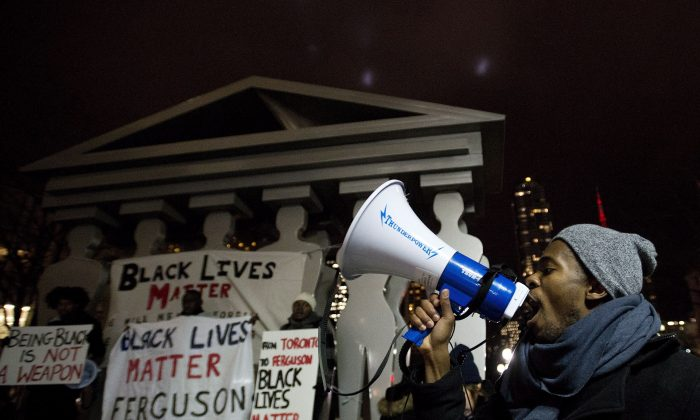 Thousands gather outside the U.S. Consulate in Toronto on Nov. 25, 2014, to protest a U.S. grand jury's decision not to indict a police officer who shot and killed Michael Brown of Feguson, Missouri. (The Canadian Press/Nathan Denette)