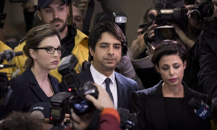 Jian Ghomeshi makes his way through a throng of media with his lawyer, Marie Henein (R), at a Toronto court on Nov. 26, 2014. Henein says the former CBC radio host plans to plead not guilty to multiple counts of sexual assault. (The Canadian Press/Darren Calabrese)