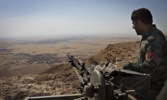 An Iraqi Kurdish Peshmerga fighter hold his position on the top of Mount Zardak, a strategic point taken 3 days ago, about 25 kilometres east of Mosul on Sept. 9, 2014. (J.M. Lopez/AFP/Getty Images)