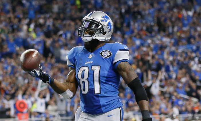 Detroit Lions wide receiver Calvin Johnson tosses the ball after his 25-yard reception for a touchdown during the first half of an NFL football game against the Chicago Bears in Detroit, Thursday, Nov. 27, 2014. (AP Photo/Rick Osentoski)