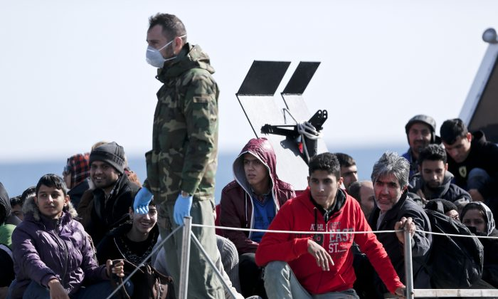 A Greek coast guard officer, wearing a mask for fear of infectious disease, stands next to a small group of immigrants, on a launch carrying them to shore from a crippled smuggling ship with more than 600 people, at the coastal Cretan port of Ierapetra, Greece, on Thursday, Nov. 27, 2014. The ship, whose passengers are mostly Syrians,  including children, women and elderly men, suffered engine failure 70 nautical miles off Ierapetra on Tuesday. The migrants will be given temporary shelter at an Ierapetra indoor basketball stadium. (AP Photo/Petros Giannakouris)