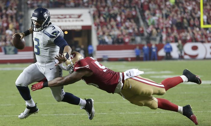 San Francisco 49ers linebacker Ahmad Brooks, right, dives to tackle Seattle Seahawks quarterback Russell Wilson (3) during the second quarter of an NFL football game in Santa Clara, Calif., Thursday, Nov. 27, 2014. (AP Photo/Marcio Jose Sanchez)