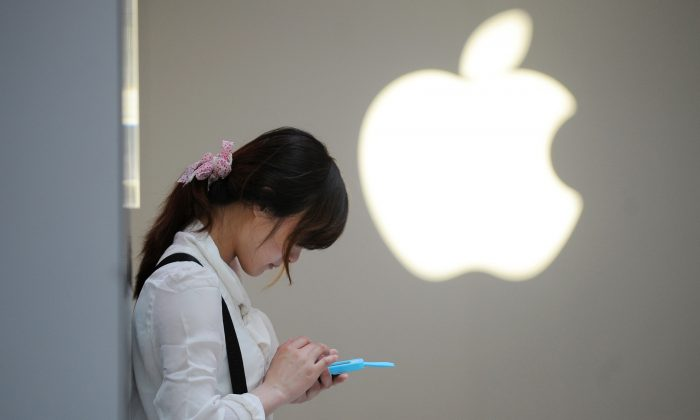 A woman uses her mobile phone outside an Apple store in Shanghai on May 7, 2012. (Peter Parks/AFP/Getty Images)