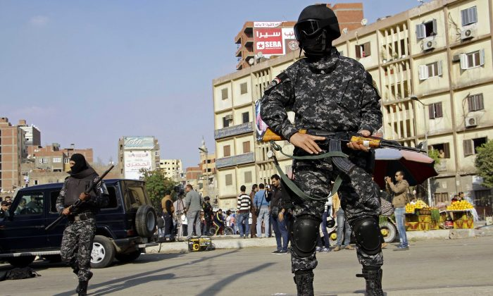 Masked Egyptian security forces deploy in the Cairo suburb of Matareya on the day that Islamists called for nationwide demonstrations Friday, Nov. 28, 2014. (AP Photo/Ahmed Abdel Fattah)