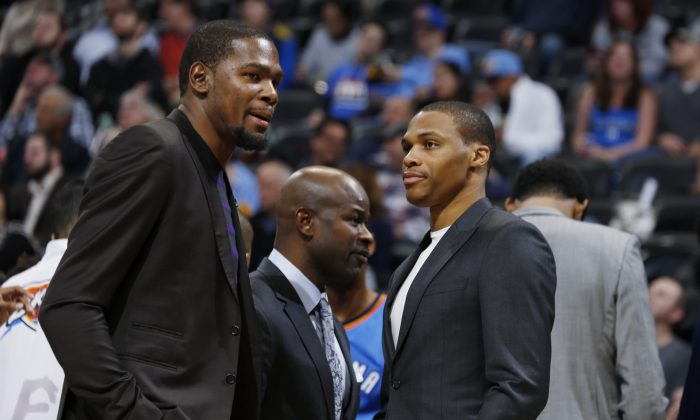 Injured Oklahoma City Thunder forward Kevin Durant, left, confers with injured guard Russell Westbrook during a timeout against the Denver Nuggets in the third quarter of the Nuggets' 107-100 victory in an NBA basketball game in Denver on Wednesday, Nov. 19, 2014. (AP Photo/David Zalubowski)