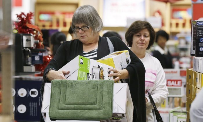 "For two years running now, people are falling for The Onion's satirical article, ""42 Million Dead In Bloodiest Black Friday Weekend On Record."" A shopper struggles with boxes as she loads a cart in an aisle at a Kohl's department store in Sherwood, Ark., Thanksgiving evening Thursday, Nov. 27, 2014. Early-bird shoppers headed to stores on Thanksgiving in what's becoming a new holiday tradition. (AP Photo/Danny Johnston)"