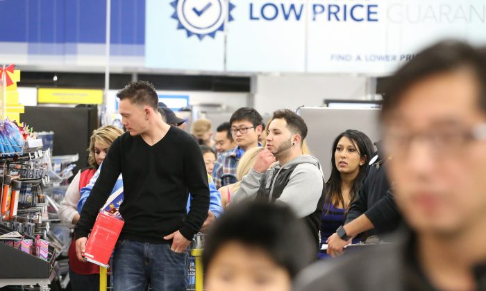 Shoppers wait to pay for items during a Thanksgiving day sale at a Best Buy store in Broomfield, Colo., on Thursday, Nov. 27, 2014. (AP Photo/Brennan Linsley)