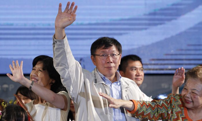 Taipei's new mayor-elect Ko Wen-je, center, waves to supporters at his campaign headquarters in Taipei, Taiwan, Saturday, Nov. 29, 2014. (AP Photo/Wally Santana)