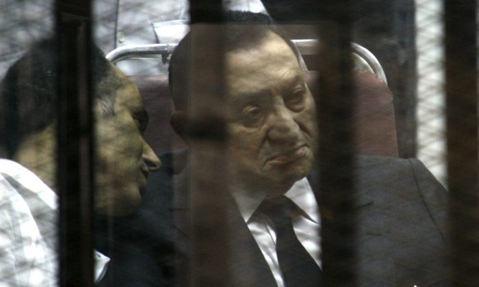 Ousted Egyptian President Hosni Mubarak sits in the defendants cage behind protective glass during a court hearing as he listens to his son Gamal, left, in Cairo, Egypt, May 21, 2014. Egypt court on Saturday, Nov. 29, dismissed criminal charges against Mubarak in the killing of more than 900 protesters during the 2011 uprising against his rule. (AP Photo/Tarek el-Gabbas)