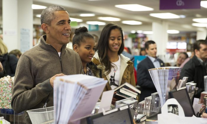 "President Barack Obama, left, shops with his daughters, Sasha, center, and Malia, at Politics and Prose bookstore for ""Small Business Saturday,"" on Saturday, Nov. 29, 2014, in Washington. (AP Photo/Evan Vucci)"