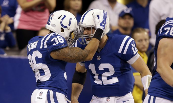 Indianapolis Colts running back Dan Herron, left, celebrates his 49-yard touchdown against the Washington Redskins with quarterback Andrew Luck during the first half of an NFL football game Sunday, Nov. 30, 2014, in Indianapolis. (AP Photo/Darron Cummings)