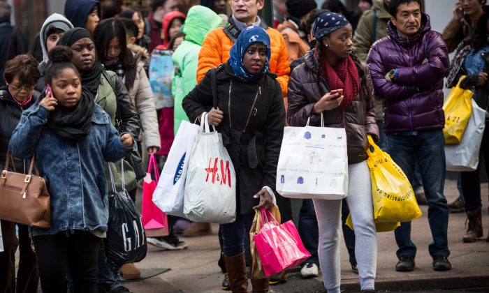 Shoppers carry recent purchases through Herald Square on the morning of November 28, 2014 in New York City. The Friday after Thanksgiving, also known as Black Friday, traditionally marks the beginning of the Holiday season. (Photo by Andrew Burton/Getty Images)