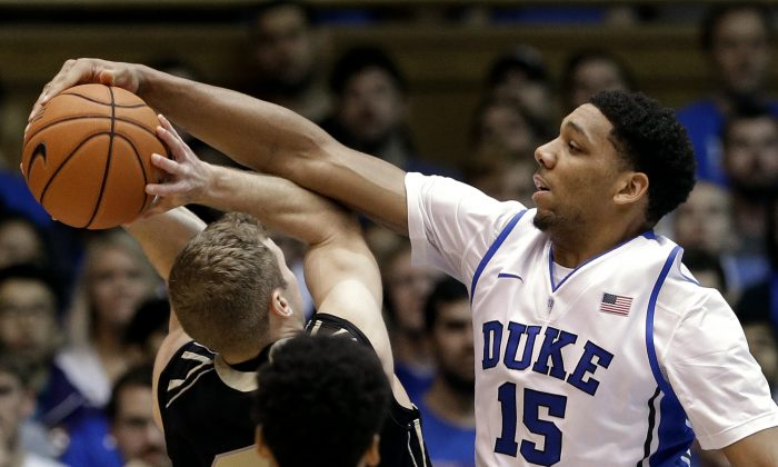 Duke's Jahlil Okafor (15) blocks Army's Kyle Wilson during the first half of an NCAA college basketball game in Durham, N.C., Sunday, Nov. 30, 2014. (AP Photo/Gerry Broome)