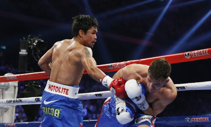 WBO welterweight champion Manny Pacquiao, left, of the Philippines lands a right on the arm of WBO junior welterweight champion Chris Algieri of the United States during their world welterweight title boxing match at the Venetian Macao in Macau, Sunday, Nov. 23, 2014. (AP Photo/Kin Cheung)