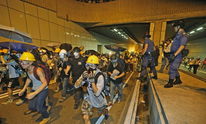 Pro-democracy protesters run away from police on the main road outside the government headquarters in Hong Kong Sunday, Nov.30, 2014. Hundreds of pro-democracy protesters faced off with Hong Kong police late Sunday, stepping up their movement for genuine democratic reforms after being camped out on the city's streets for more than two months. (AP Photo/Kin Cheung)