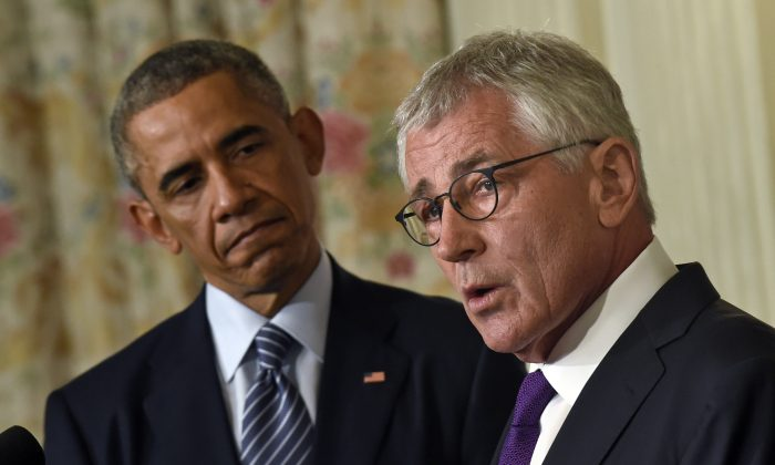 President Barack Obama looks to Defense Secretary Chuck Hagel as Hagel talks about his resignation during an event in the State Dining Room of the White House in Washington, Nov. 24, 2014. (AP Photo/Susan Walsh)