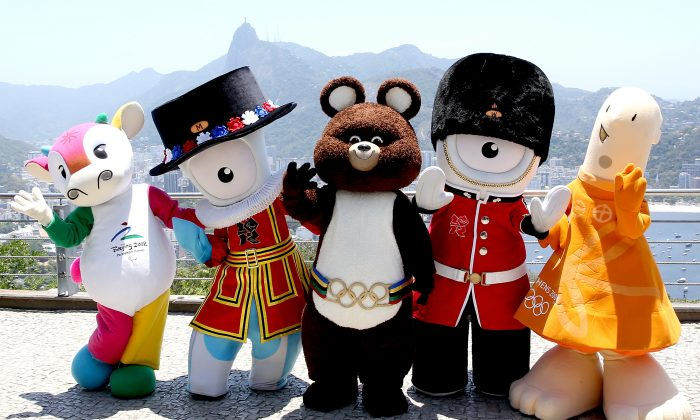 Fu Niu Lele, the mascot from the Beijing Olympic Games; Mandeville, the mascot from the London Olympic Games; Misha, the mascot from the Moscow Olympic Games; Wenlock, the mascot from the London Olympic Games; and Athene, the mascot from the Athens Olympic Games, pose for a picture after meeting the children from the Vila Olímpica de Pedra de Guaratiba project atop Morro da Urca in Rio de Janeiro on Nov. 21, 2014. (Matthew Stockman/Getty Images)