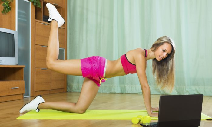 Cheerful young woman working out with notebook in gym