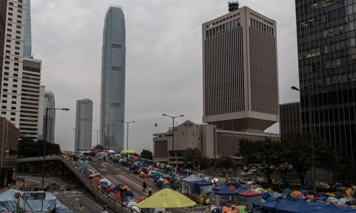 Pedestrians and protesters walk on a section of Harcourt Road, a multi-lane highway through the heart of the financial district currently blocked by pro-democracy protester barricades and hundreds of tents, in the Admiralty district of Hong Kong Kong on December 1, 2014. (Anthony Wallace/AFP/Getty Images)