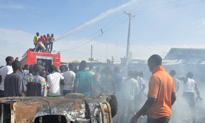In this Tuesday, July , 2014 file photo, People gather at the scene of a car bomb explosion, at the central market, in Maiduguri, Nigeria. (AP Photo/Jossy Ola)