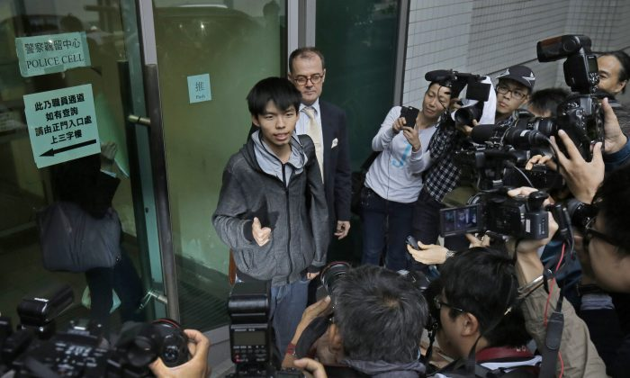 Prominent Hong Kong student protest leader Joshua Wong, center, walks out from a court with his lawyer in Hong Kong, Thursday, Nov. 27, 2014. (AP Photo/Vincent Yu)