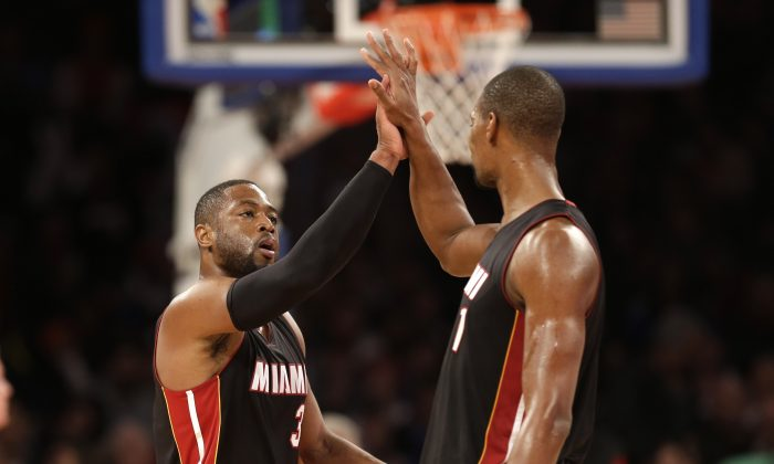 Miami Heat's Dwyane Wade, left, celebrates with Chris Bosh during the second half of the NBA basketball game, Sunday, Nov. 30, 2014 in New York. The Heat defeated the Knicks 86-79. (AP Photo/Seth Wenig)