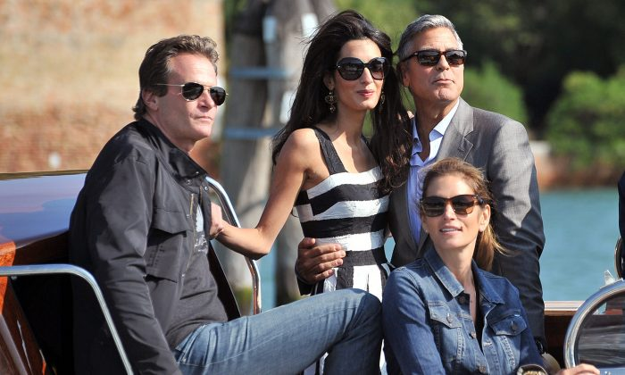 George Clooney, top right, Amal Alamuddin, Cindy Crawford, bottom right and her husband Rande Gerber arrive in Venice, Italy, Friday, Sept. 26, 2014. (AP Photo/Luigi Costantini)