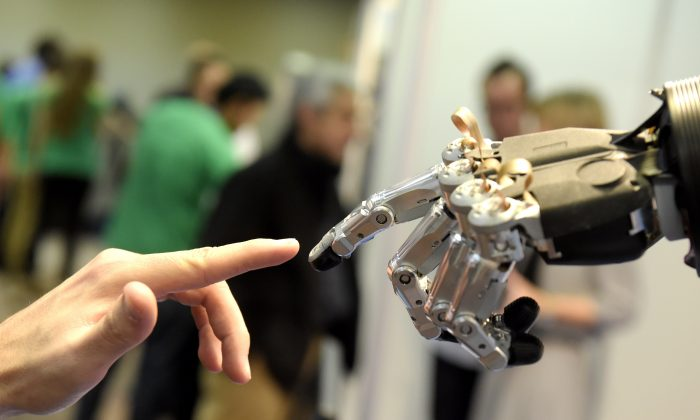 A man moves his finger toward SVH (Servo Electric 5 Finger Gripping Hand) automated hand made by Schunk during the 2014 IEEE-RAS International Conference on Humanoid Robots in Madrid on November 19, 2014. (Gerard Julien/AFP/Getty Images)