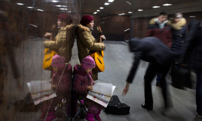 Ksenya, a street musician from a village in Kaluga region, about 160km (100 miles) from Moscow, plays guitar to earn money in an underground subway with her daughter in Moscow, Russia, on Dec. 17, 2014. She earns about 3000 Rubles (about $ 46 USD) a day and works a few days a month to make ends meet. The ruble's fall, the plunge in world oil prices and the sanctions' denial of access to Western credit have all dealt a blow to the Russian economy. (AP Photo/Alexander Zemlianichenko)