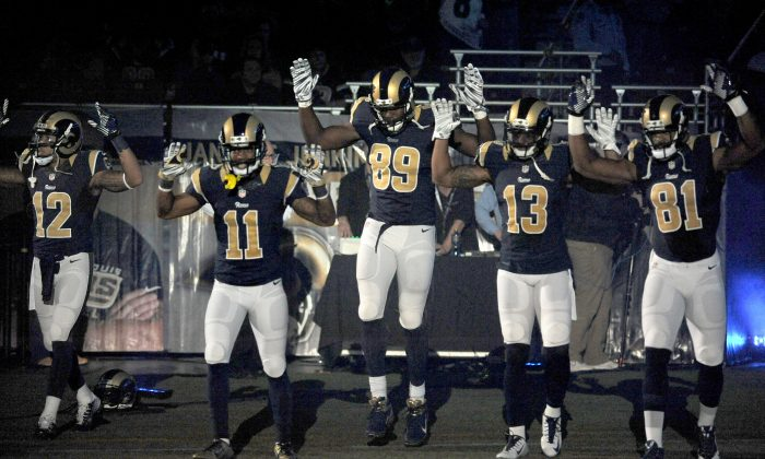 "Members of the St. Louis Rams raise their arms in awareness of the events in Ferguson, Mo., as they walk onto the field during introductions before an NFL football game against the Oakland Raiders, Sunday, Nov. 30, 2014, in St. Louis. From left are Stedman Bailey (12), Tavon Austin (11), Jared Cook, (89) Chris Givens (13) and Kenny Britt (81). The players said after the game, they raised their arms in a ""hands up"" gesture to acknowledge the events in Ferguson. (AP Photo/L.G. Patterson)"