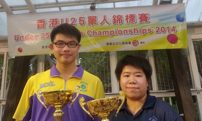 James Tang (left) of the Hong Kong Youth Team and Vivian Yip from Hong Kong Football Club proudly displays their Under-25 Singles trophies at Taipo Waterfront Park, on Sunday Nov 30, 2014. (Howard Poon)