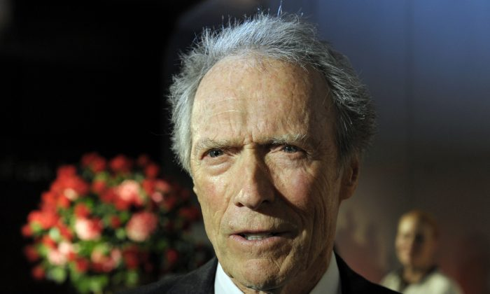 """FILE - In this Feb. 1, 2012 file photo, actor and director Clint Eastwood speaks with reporters during the opening of the Warner Bros. Theater at the Smithsonian National Museum of American History in Washington. The National Board of Review thrust its support squarely behind the early 1980s New York drama """"A Most Violent Year,"""" naming it best film and awarding its stars Oscar Isaac and Jessica Chastain. Announcing its annual selections on Tuesday, Dec. 2, 2014, the group also handed best director to Eastwood for his upcoming Navy SEAL drama """"American Sniper."""" (AP Photo/Cliff Owen, File)"""