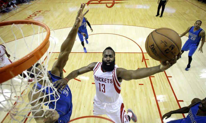 Houston Rockets guard James Harden (13) goes up for a shot as Dallas Mavericks' Brandan Wright (34) defends during the first half of an NBA basketball game Saturday, Nov. 22, 2014, in Houston. (AP Photo/David J. Phillip)