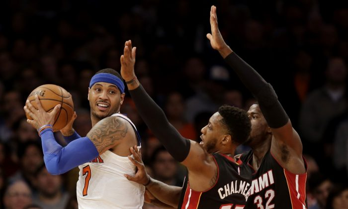 New York Knicks' Carmelo Anthony, left, looks to pass around Miami Heat's James Ennis, right, and Mario Chalmers during the first half of the NBA basketball game, Sunday, Nov. 30, 2014 in New York. (AP Photo/Seth Wenig)