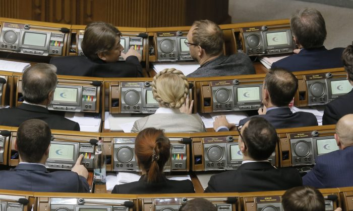 Former Prime Minister and leader of the Fatherland party Yulia Tymoshenko (C) and lawmakers from her party vote during a parliament session in Kiev, Ukraine, Tuesday, Dec. 2, 2014. Ukraine's parliament has approved the formation of a new government, bringing an end to weeks of behind-the-scenes political wrangling following an October election that ushered in a group of ardently pro-Western parties. (AP Photo/Efrem Lukatsky)