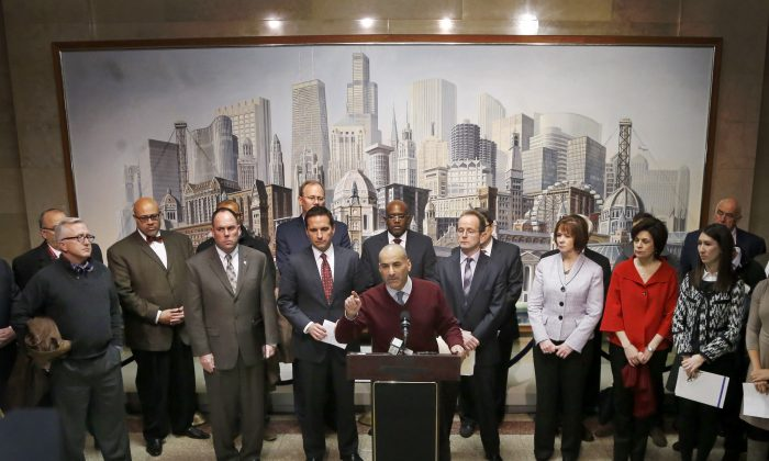 Sam Toia (C), president of the Illinois Restaurant Association, leads Aldermen, merchants, and business leaders in a news conference voicing opposition to a proposed increase of Chicago's minimum wage to $13 an hour Monday, Dec. 1, 2014, in Chicago. Chicago is set to become the latest US city to raise its minimum wage, as Mayor Rahm Emanuel fast-tracks a politically popular plan to reach $13 per hour amid his bid for a second term and criticism that he's out-of-touch with working people. (AP Photo/Charles Rex Arbogast)
