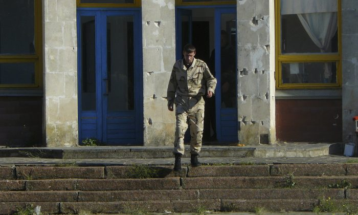 A man in camouflage guards and chases away any would-be visitors at the Dobrobut farm in Grabovo, Crimea, on Oct. 28, 2014. Dobrobut was one of dozens of businesses to be forcibly taken over this year by Crimea's new pro-Moscow leaders. (AP Photo/Laura Mills)
