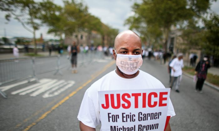 The son of Eric Garner, the man who died after being placed in a chokehold by an NYPD officer in July, said there's going to be no riots in New York City. Al Smoot marches during a rally on Staten Island, N.Y., on Aug. 23, 2014 following the death of Eric Garner as a result of an apparent chokehold by an NYPD officer. The NYPD is preparing for potential protests ahead of a Staten Island grand jury decision whether to indict a police officer in the death of Eric Garner. (Yana Paskova/Getty Images)
