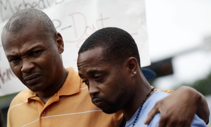 Louis Head (R), stepfather of 18 year-old Michael Brown, and Brown's cousin Eric Davis (L) attend a news conference on Aug. 15, 2014 in Ferguson, Mo. Michael Brown was killed in broad daylight on Aug. 9, 2014, with witnesses and law enforcement providing conflicting accounts of how the 18-year-old lost his life. (Joshua Lott/AFP/Getty Images)