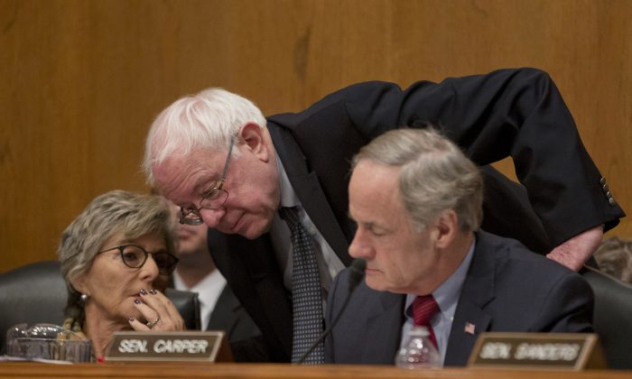 Senate Environment and Public Works Committee Chair Sen. Barbara Boxer (D-Calif.) left, confers with Sen. Bernie Sanders (I-Vt.) center, and Senate subcommittee on Clean Air and Nuclear Safety Chairman Sen. Tom Carper (D-Del.) on Capitol Hill in Washington on Jan. 30, 2014. (AP Photo)